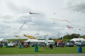 A kite flying display taking place behind Country Fest